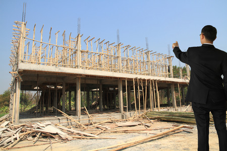 supervise: Businessman in building construct area cement pillar and wood  Stock Photo