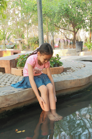 Asian girl soak her feet in hot springs to relax.