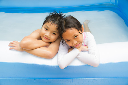 Kids play swim in inflatable plastic pool. photo