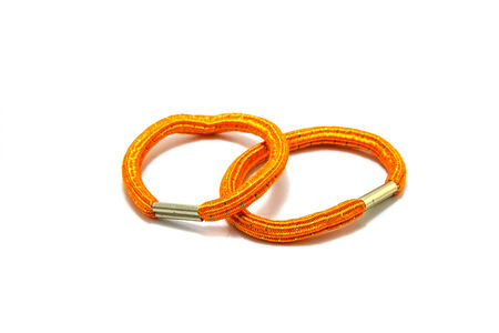 Orange rubber band on a white background.  photo