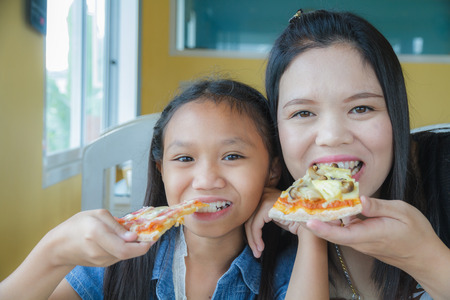bacon portrait: Mother and daughter eating pizza in restaurant.