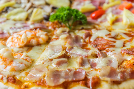 Pizza with ham, mushroom, bacon and salami in restaurant. photo
