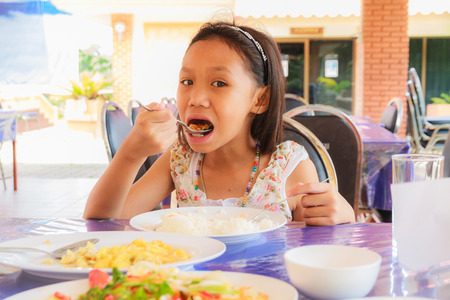 Asian girl eating rice and food on table in restaurant. photo