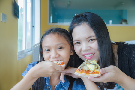 Mother and daughter eating pizza in restaurant. photo