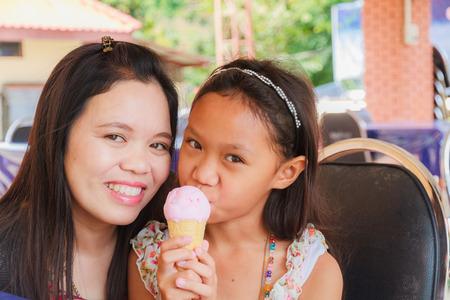 Asian girl eating Ice Cream Cone in restaurant. photo