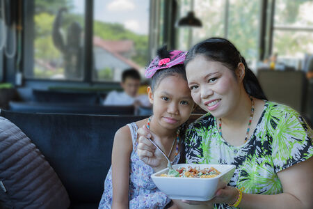Mother and daughter eating Caesar salad in restaurant photo