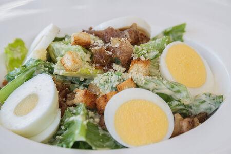 Caesar salad on white dish in restaurant photo