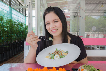 Girl eating Caesar salad in the restaurant photo