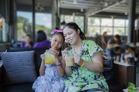 Mother and daughter drinking orange juice and ice coffee in restaurant photo