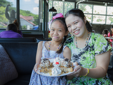 Mother and daughter eat Honey toast in restaurant photo