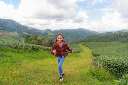 Asia girl run in Tea plantation on mountain at north Thailand. photo