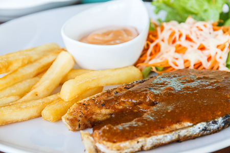 Fish salmon steak, french fries and salad on white plate. photo