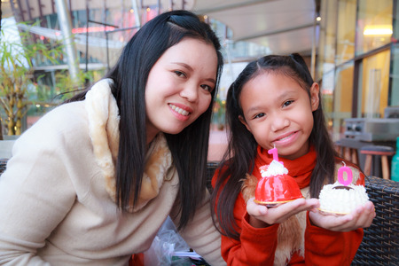 Mother and daughter hold Strawberry cake and White Chocolate cake in a restaurant. photo