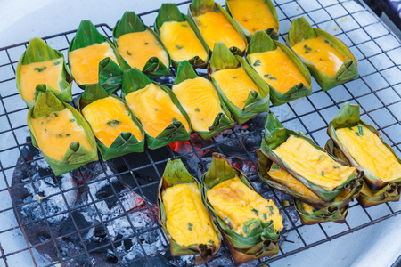 thailand culture: Grilled egg in cup made banana leaves on stove in market northern Thailanl. Thailand call Kai Pam. Stock Photo