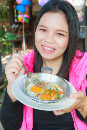 Asia woman eating Egg pan in restaurant. photo