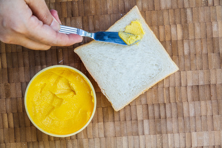 Sandwich bread, Butter and butter knife on wooden table. Top view. Standard-Bild