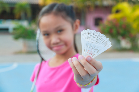 Cute little girl holding badminton racket and shuttlecock, Outdoor. photo