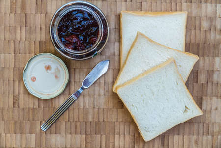 Sandwich bread, Cherry jam and Jam knife on wooden table. Top view. photo