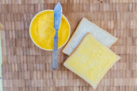 Sandwich bread, Butter and butter knife on wooden table. Top view. Stock Photo
