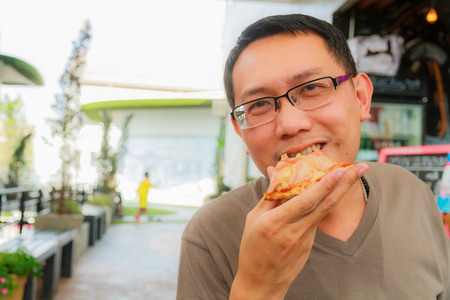 Asian man eat pizza in a restaurant photo