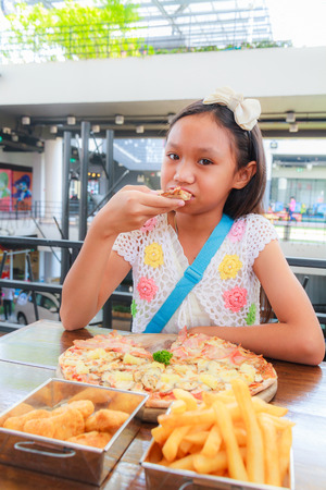 bacon portrait: Asian girl child eat pizza in a restaurant