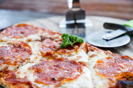 Salami pizza on wood tray and pizza cutter in restaurant. photo