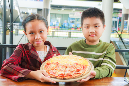 Asain boy and girl hold pizza meat lover and cheese in restaurant. Stock Photo