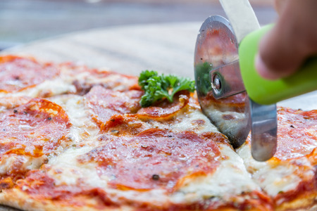 wood cutter: Salami pizza on wood tray and pizza cutter in restaurant.