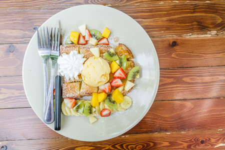 Honey toast with ice cream vanilla, kiwi, mango, banana, apple and strawberry on white plate. photo