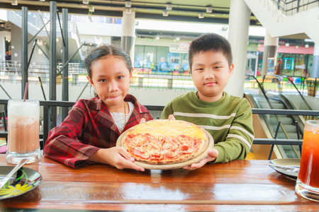 meat lover: Asain boy and girl hold pizza meat lover and cheese in restaurant. Stock Photo