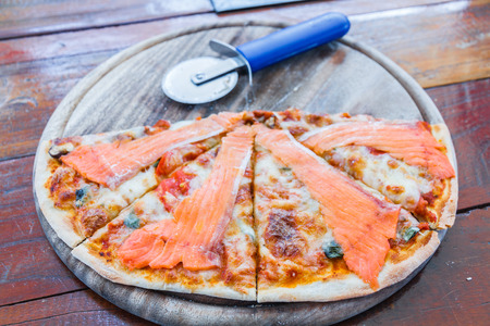 wood cutter: Salmon pizza on wood tray and pizza cutter in restaurant.