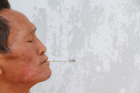 asian old man: Asian old man smoking cigarette. Face filled with wrinkles. Stock Photo