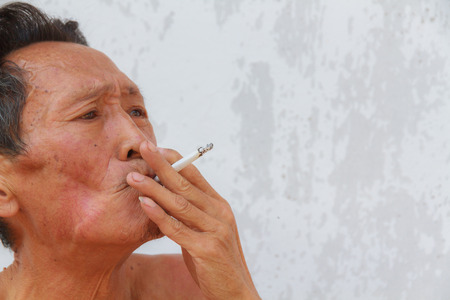 Asian old man smoking cigarette. Face filled with wrinkles. photo