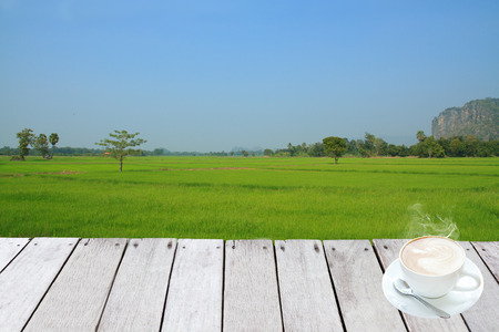 Plank wooden and coffee front Paddy rice field at north Thailand. photo