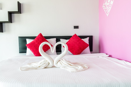 heart suite: Towels shaped swans heart on bed in room hotel.
