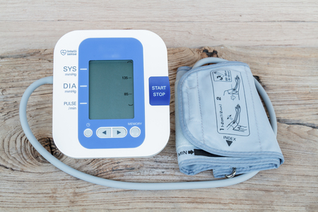 diastolic: Automatic blood pressure monitor on wood table.