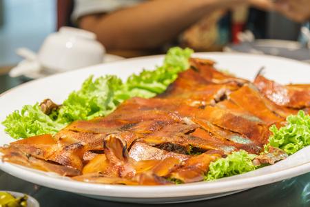 spanferkel: Gegrilltes Spanferkel bei China-Restaurant zu Pflanze abgeschnitten.