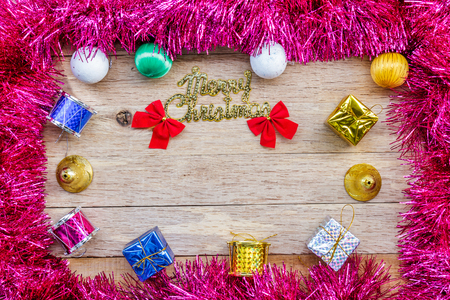 tassel: Xmas day: Merry Christmas decoration with gift box, ball, bell, drum, bow and tassel on wood background. Top view.