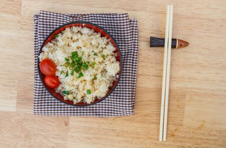chinese meal: Garlic fried rice add tomato and chopsticks on wooden table. Top view. Stock Photo