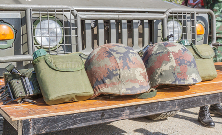 green plastic soldiers: Helmet military and Military flask on wooden table.