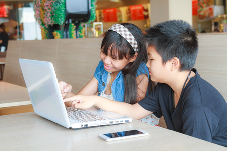 Asian girl and boy use laptop and smartphone in canteen. photo