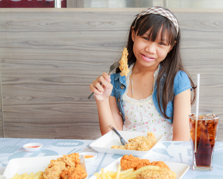 Asia girl child eat fried chicken and sparkling water in restaurant.