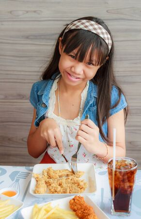 Asia girl child eat fried chicken and sparkling water in restaurant. photo