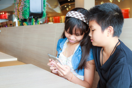 Asian boy and girl use smartphone in canteen. photo