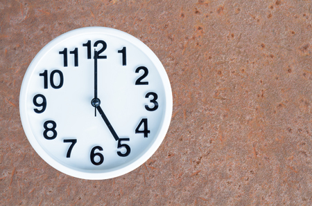 pm: Clock show 5 am or pm on steel rusty background with copy space.