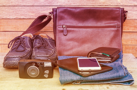 outfits: Travel casual outfits with travel accessory on wooden table, vintage travel concept.