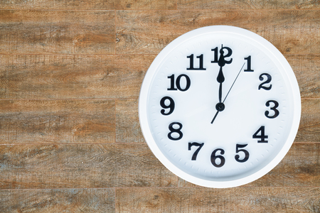 Clock show 12 am or pm on wood background with copy space. clipping path in picture. Foto de archivo