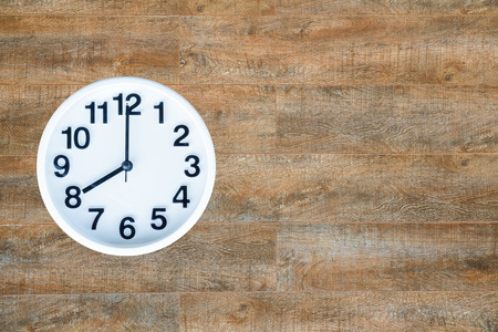 pm: Clock show 8 am or pm on wood background with copy space.