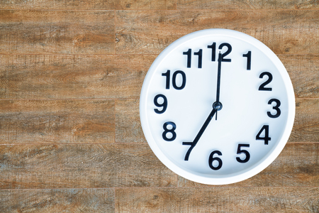 pm: Clock show 7 am or pm on wood background with copy space.