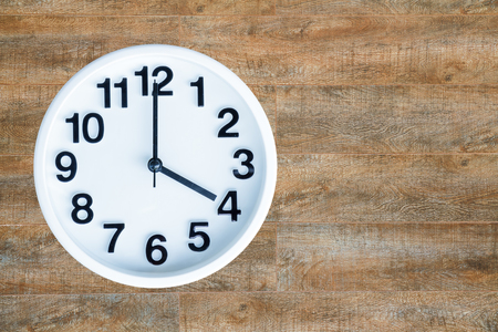pm: Clock show 4 am or pm on wood background with copy space. Stock Photo